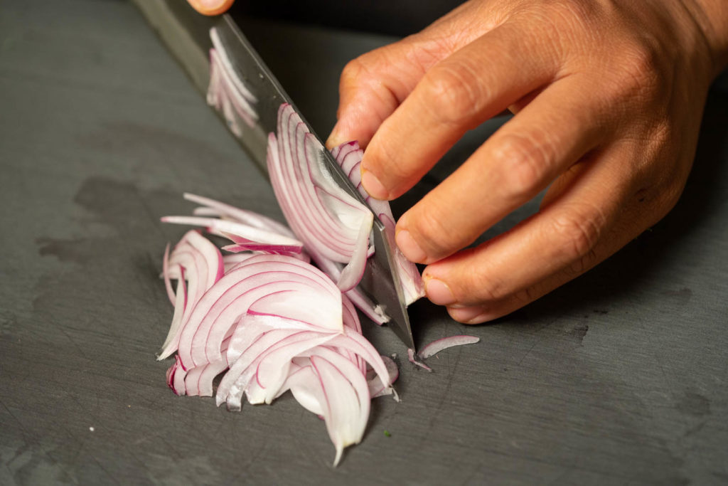 Thinly slice red onions