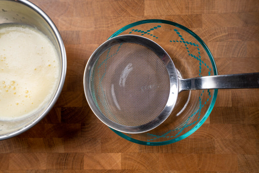 Strain egg pudding mix into container